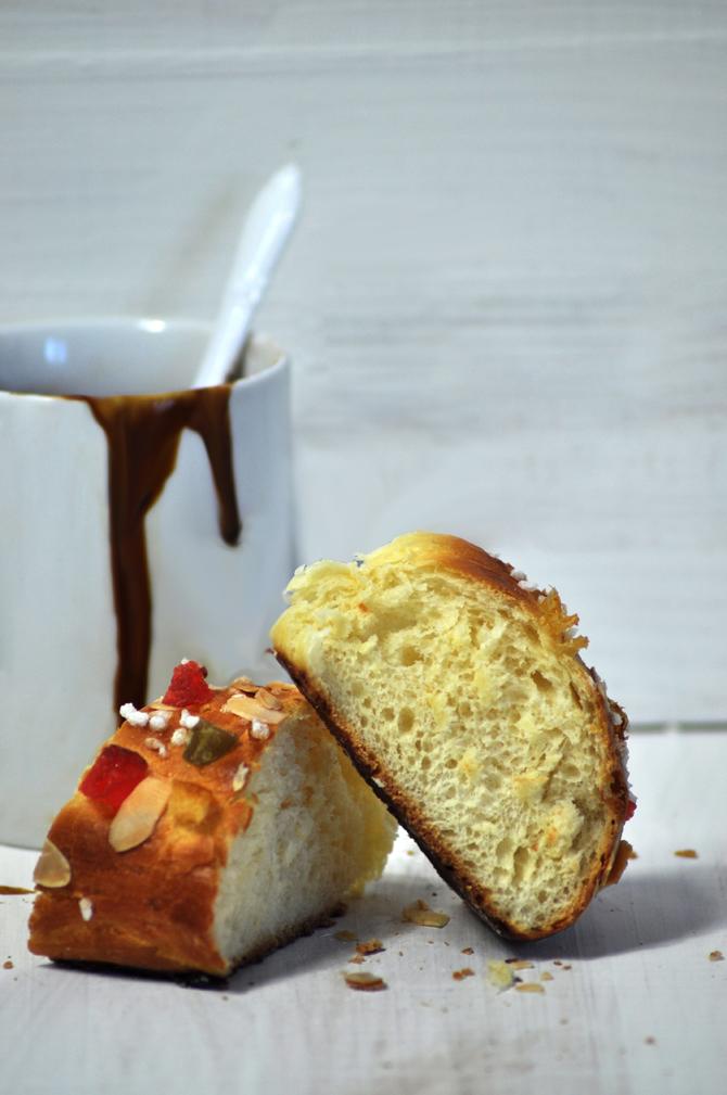 Roscón de reyes decorado con fruta confitada y azúcar en perlas y acompañado con una taza de chocolate caliente.